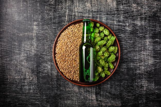 Una bottiglia di birra su un grano verde fresco e grano in un piatto contro lo sfondo