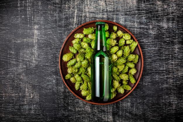Una bottiglia di birra su un luppolo fresco verde in un piatto contro lo sfondo di una lavagna graffiata nera