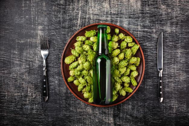 Una bottiglia di birra su un luppolo verde fresco in un piatto con coltello e forchetta contro lo sfondo