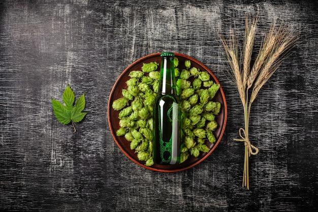 Una bottiglia di birra su un luppolo verde in un piatto con spighette e foglia di luppolo di grano sullo sfondo di una lavagna nera graffiato