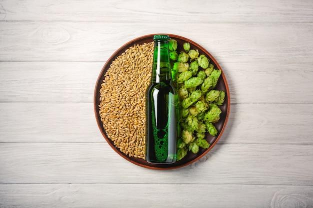 Una bottiglia di birra su un piatto con luppolo verde e grano di avena su un bordo di legno bianco