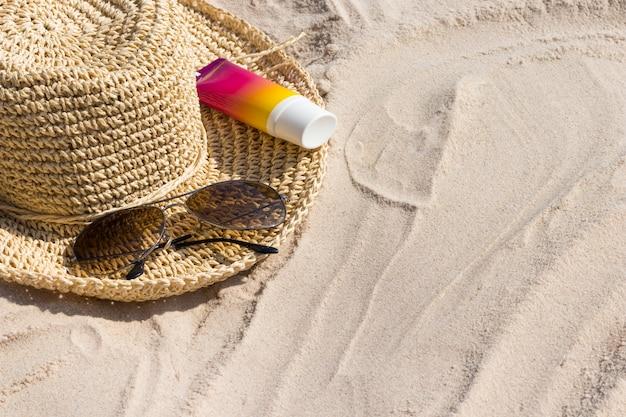 Una bottiglia di crema solare con occhiali da sole e cappello panama su una spiaggia