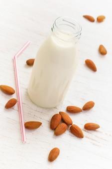 Una bottiglia di latte di mandorle sullo sfondo di mandorla