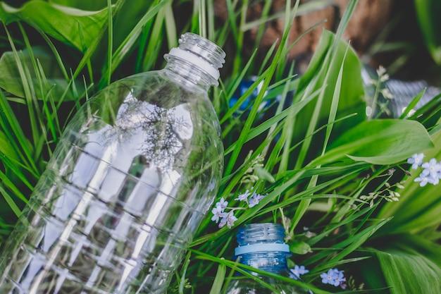 Una bottiglia di plastica giace sull'erba a terra, inquinamento ambientale, immondizia, rifiuti