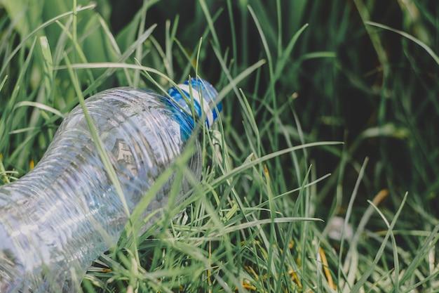 Una bottiglia di plastica giace sull'erba a terra, inquinamento ambientale, rifiuti di plastica