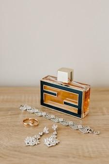 Una bottiglia di profumo, un braccialetto, orecchini a bottone e fedi nuziali su un tavolo di legno contro una parete chiara