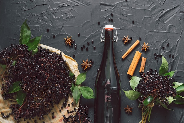Una bottiglia di sciroppo di sambuco su uno sfondo scuro con bacche di sambuco fresche, cannella e anice stellato.