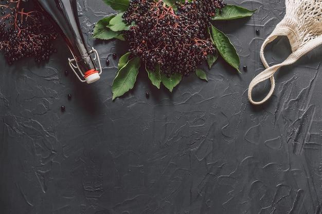 Una bottiglia di sciroppo di sambuco su uno sfondo scuro con bacche di sambuco fresche e sacchetto di stringa.
