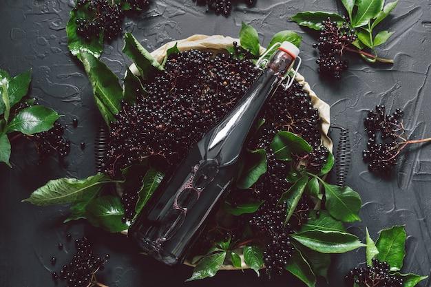 Una bottiglia di sciroppo di sambuco su uno sfondo scuro con bacche di sambuco fresche.