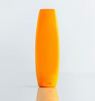 Una bottiglia di shampoo arancione vista frontale sul muro bianco