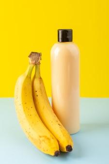 Una bottiglia di shampoo di plastica color crema vista frontale con tappo nero isolato insieme a banane sullo sfondo giallo-blu-azzurro cosmetici capelli bellezza