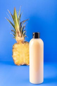 Una bottiglia di shampoo di plastica color crema vista frontale può con tappo nero isolato con ananas a fette sui capelli blu bellezza cosmetici sfondo