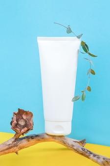 Una bottiglia di tubo cosmetico in bianco bianco sul bastone di legno con fiori secchi e ramo di eucalipto
