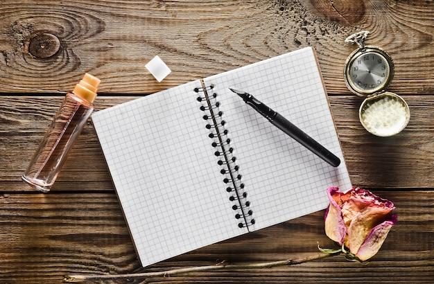 Una bottiglia di vetro con profumo, taccuino e penna, rosa asciutta, orologio da tasca vintage su un tavolo di legno rustico. vista dall'alto.
