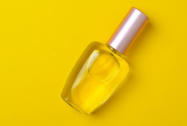 Una bottiglia di vetro di profumo femminile si trova su uno sfondo di carta gialla. vista dall'alto. tendenza del minimalismo.
