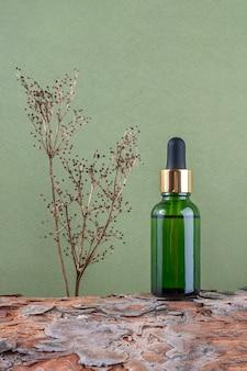 Una bottiglia di vetro verde con siero, olio essenziale o altro prodotto cosmetico e pianta di fiori secchi sulla corteccia degli alberi contro il verde