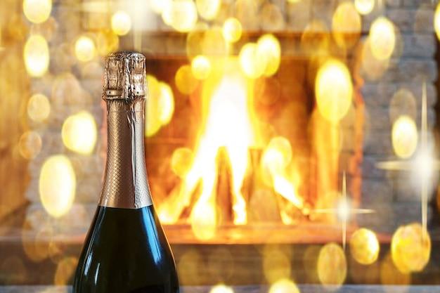 Una bottiglia di vino champagne e luci di natale bokeh vicino accogliente caminetto.