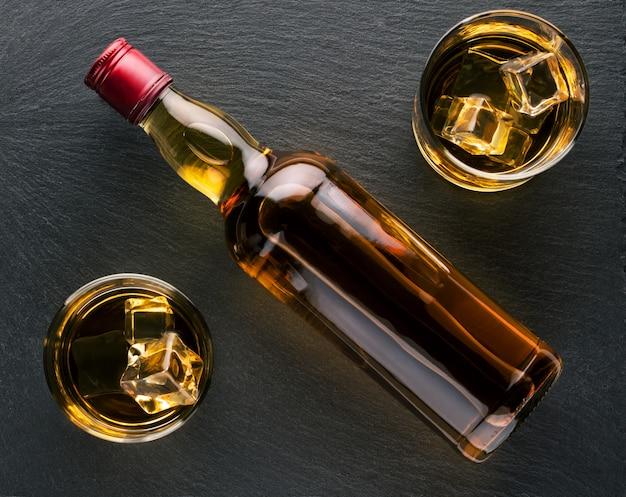 Una bottiglia di whisky tra due bicchieri