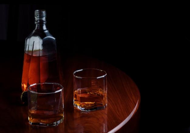 Una bottiglia e bicchieri di liquore sul tavolo di legno