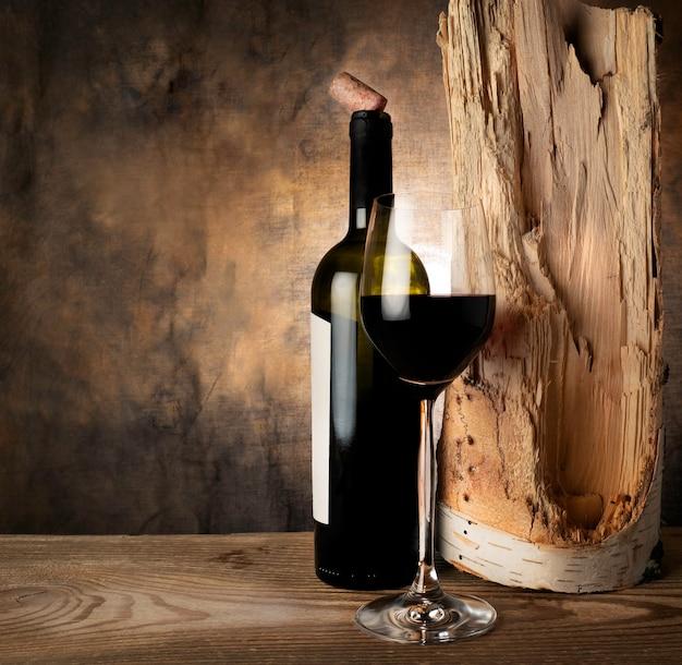 Una bottiglia e un bicchiere di vino rosso secco su un legno