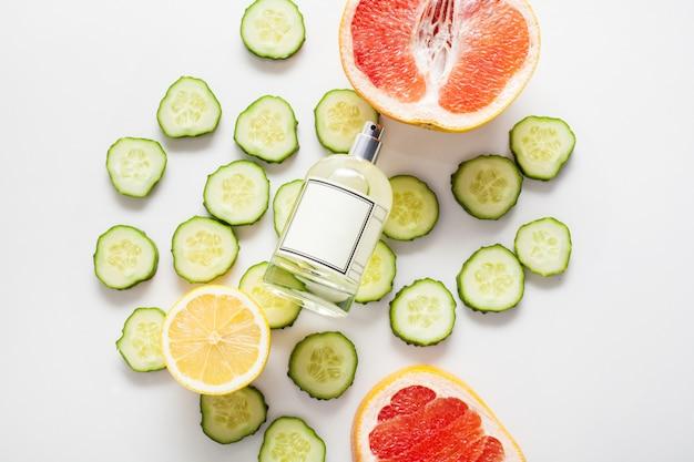 Una bottiglia per profumo o olio profumato, contro una parete di cetrioli freschi e agrumi tra cui limone e pompelmo. ingredienti concettuali di aromi freschi, aromaterapia.