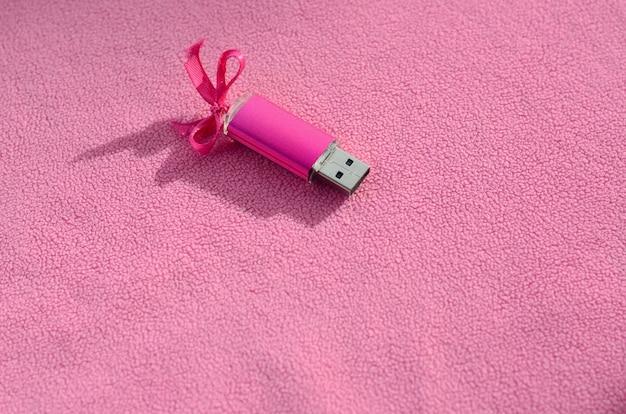 Una brillante memory card usb rosa con un fiocco rosa giace su una coperta di morbido e felpato tessuto rosa chiaro.