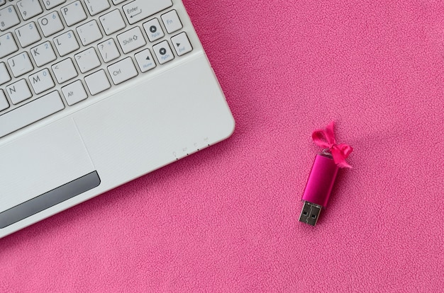 Una brillante memory card usb rosa con un fiocco rosa si trova su una coperta di morbido e felpato tessuto di pile rosa chiaro accanto a un computer portatile bianco. classico regalo femminile per una memory card