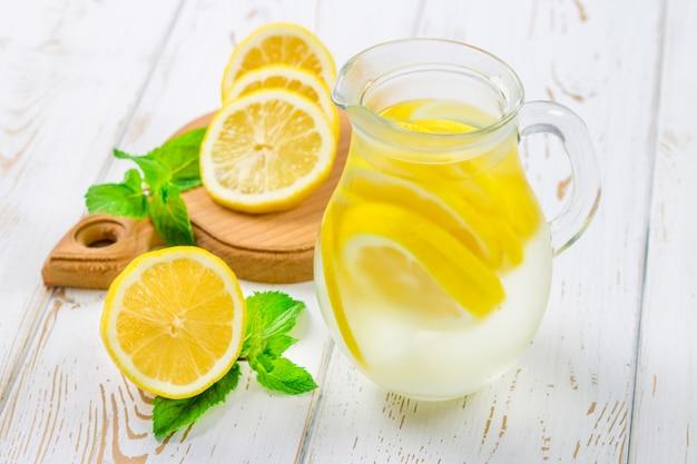 Una brocca con una limonata fredda su uno sfondo di legno bianco circondato da limoni.