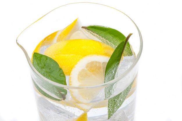 Una brocca piena di drink da ghiaccio, lobuli di limone giallo succoso fresco e acqua cristallina.