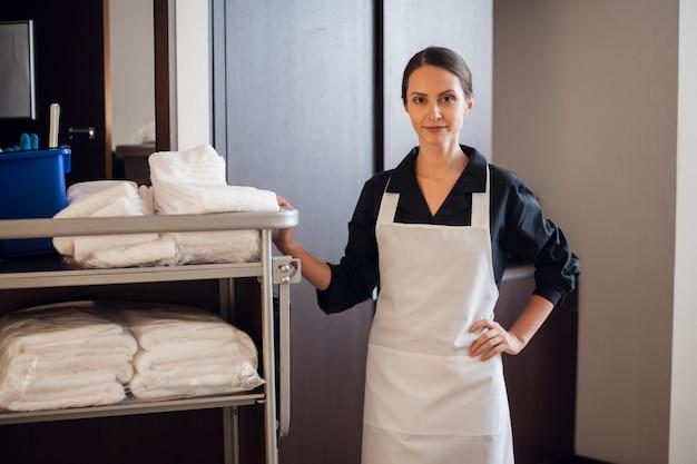 Una cameriera d'albergo sorridente in piedi con un carrello delle pulizie in un corridoio