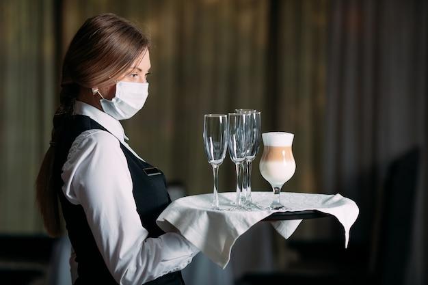 Una cameriera di aspetto europeo in maschera medica serve caffè latte.