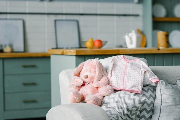 Una camicetta per bambino è sdraiata sul divano e una lepre giocattolo rosa morbida è seduta accanto ad essa. copiare lo spazio