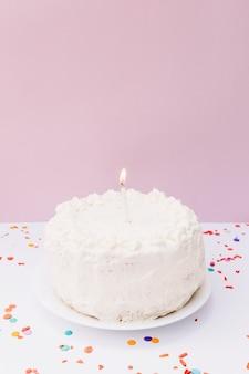 Una candela illuminata sulla torta di compleanno bianca sopra il piatto contro fondo rosa
