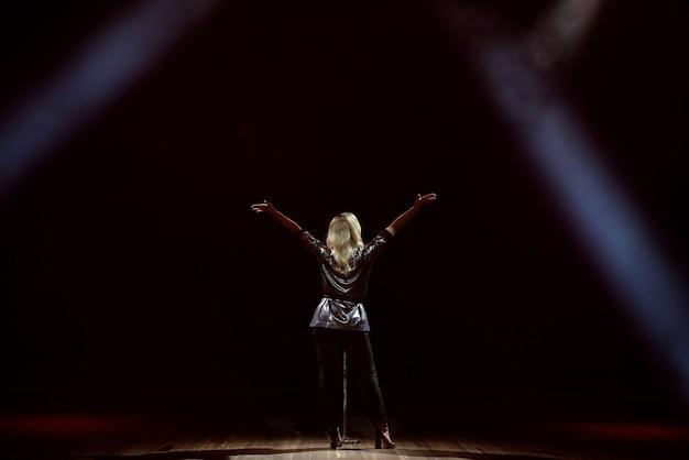 Una cantante giovane donna sul palco durante una vista di concerto dal retro.