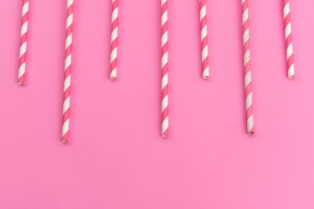 Una caramella rosa-bianca con vista dall'alto attacca deliziosa appiccicosa sul colore rosa, zucchero candito dolci