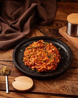 Una carne macinata di pomodoro vista frontale fritta e calda all'interno della banda nera sulla carne del pasto del cibo della tavola di legno