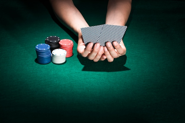 Una carta da gioco della tenuta della mano della persona con l'impilamento dei chip di poker sulla tavola del casinò