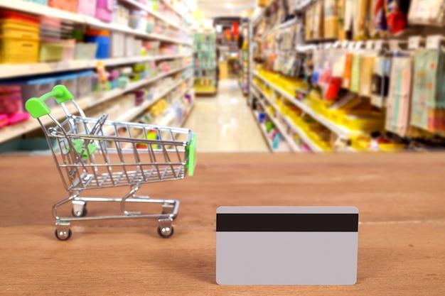Una carta di credito e un carrello per acquistare o pagare denaro al supermercato. concetto di tecnologia.