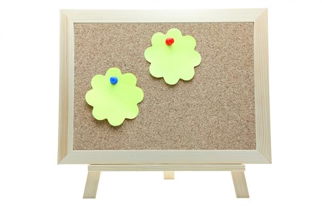Una carta di due appunti di forma del fiore sul bordo del sughero su fondo bianco