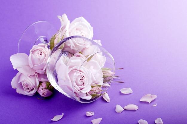 Una cartolina, o modello di invito con bella composizione floristica di rose lilla nel bicchiere.
