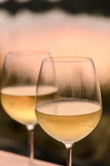 Una cena romantica in estate su una spiaggia al tramonto con due bicchieri di vino bianco