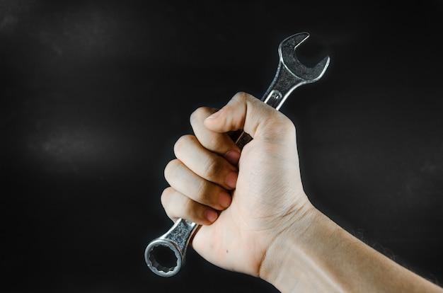 Una chiave inglese reggeva per mano dell'uomo nella luce oscura