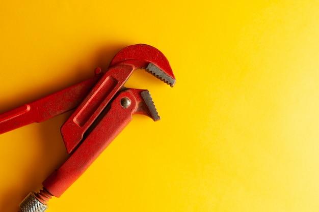 Una chiave inglese sullo sfondo giallo con alcuni connettori adatti. per il design e la decorazione