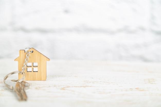 Una chiave su un portachiavi in legno a forma di casa