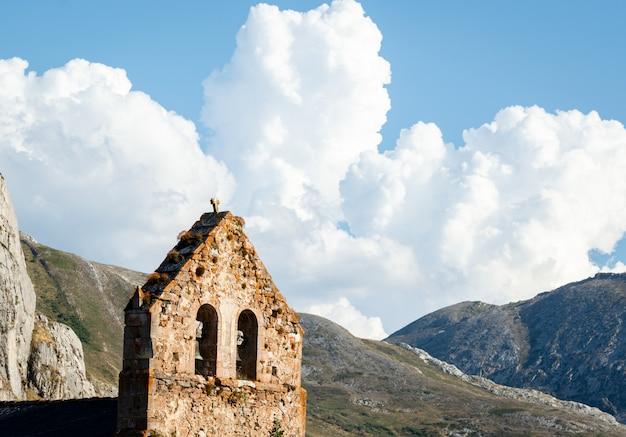 Una chiesetta in pietra con un campanile con un lieve cielo nuvoloso blu sullo sfondo durante l'estate