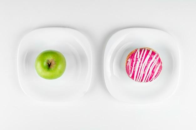 Una ciambella e una mela verde si trovano sulla vista dall'alto dei piatti, la scelta giusta. concetto resistenza alla tentazione, fast food, cibo sano, dieta.
