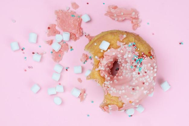 Una ciambella rosa pungente con frammenti di glassa, polvere colorata e marshmallow