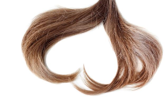 Una ciocca di capelli castano chiaro a forma di cuore da vicino