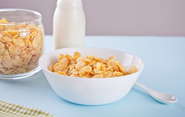 Una ciotola di cereali secchi fiocchi di mais su sfondo blu