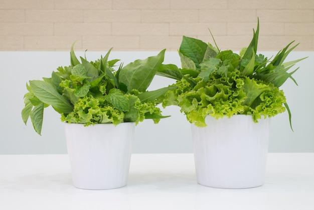 Una ciotola di foglie di lattuga verde fresco squisito su tavola bianca.